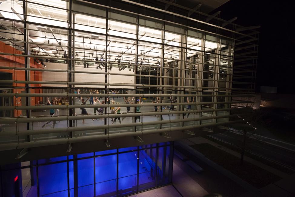 A darker shot of dancers in the upper level of the Rubenstein Arts Center.
