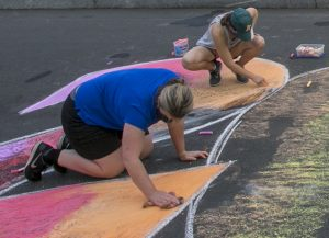 University photographer Megan Mendenhall, left, uses a crumpled plastic bag to blend the chalk by wiping it over the chalk in a circular motion.